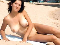 Busty Russian goddess undresses and tans at the beach