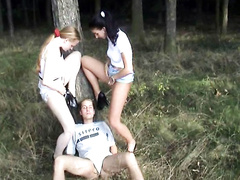 Two girls piss into his mouth outdoors
