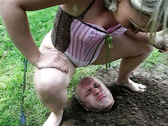 Woman pisses on the face of man buried in the dirt