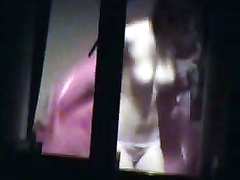 Topless girl filmed through her bedroom window