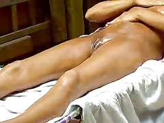 Tanning amateur rubs oil into her skin
