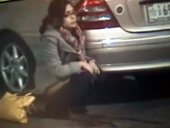 Desperate girl in glasses calmly pees on the street