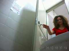 Italian milf with curly hair takes a pee in public closet