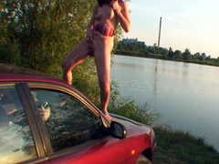 Sexy bikini girl striptease with pissing on the car
