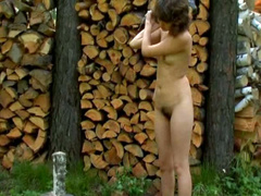 Nudist teen with small tits chops wood outdoors