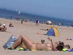Sunny day at the public beach with two nudist girls