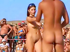Nudist men and women dance at the beach