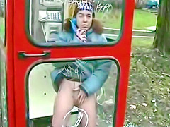 Ginger chick pisses in a phone booth in winter