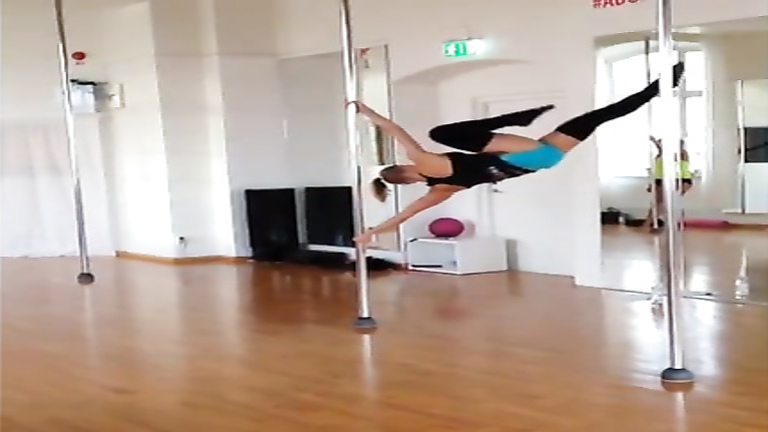 Stunningly fit girl swings around the pole