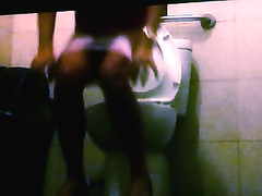 Ebony lady does a half squat and urinates in the public toilet