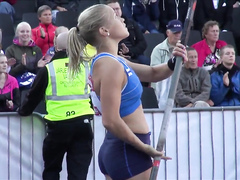 Hot blonde pole vaulter competes at a packed stadium