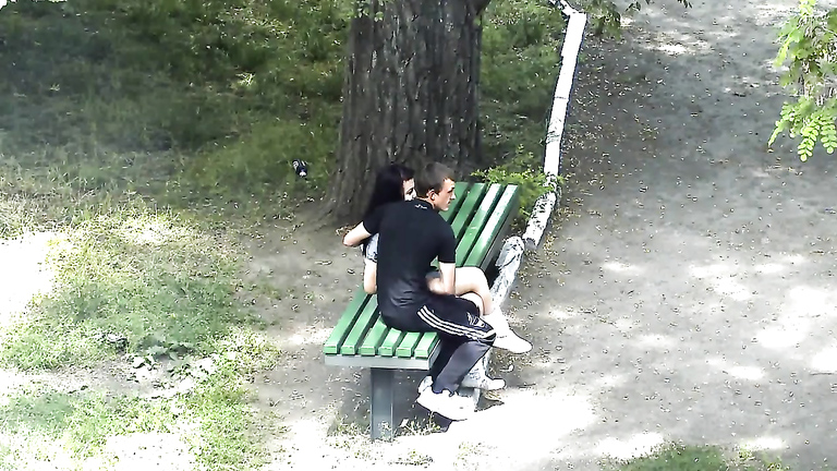 Russian lovers kiss and caress each other in the city park