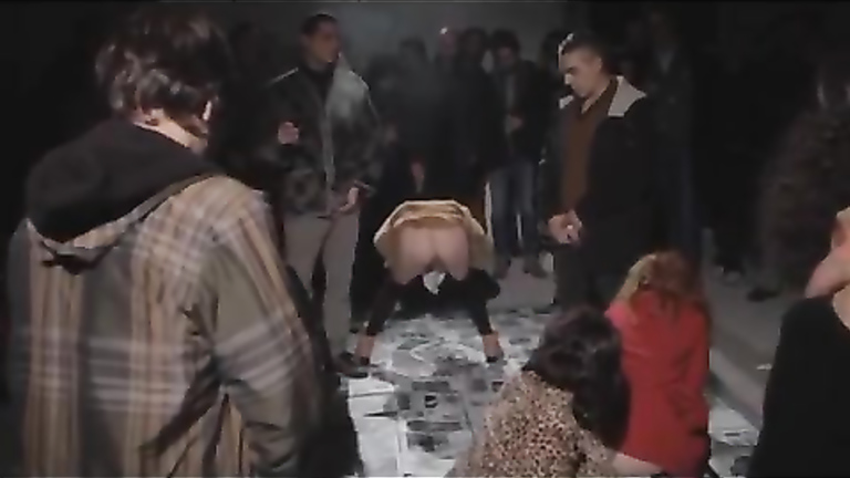 Female protesters pee on newspapers in front of other people