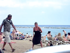 Crazy woman decides to piss on the beach sand