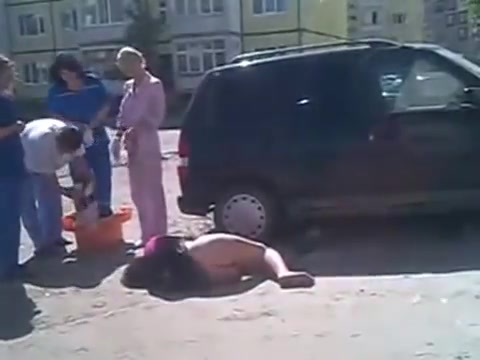 Drunken girl lies on the road with her ass naked
