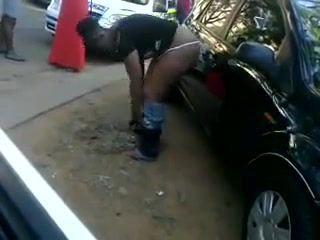 Drunken ebony woman soaks the ground with piss