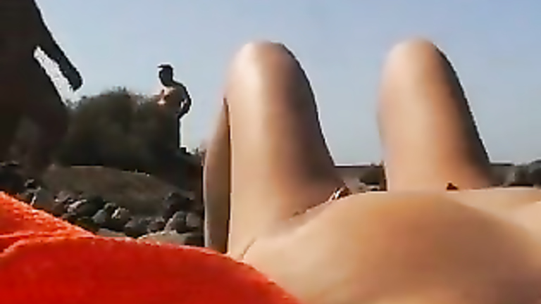 My wife enjoys fingering her sensitive clitoris at the beach