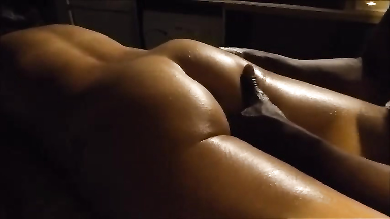 My relaxed wife has her buttocks rubbed by an African masseur