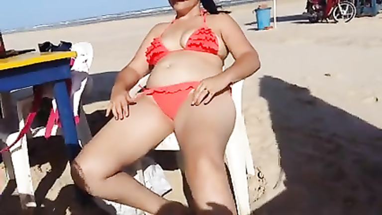 Chubby woman sets up her red bikini at the beach