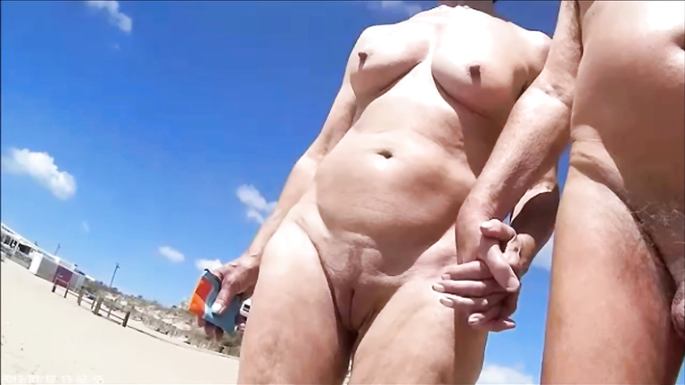 Group of mature nudists walks around the beach naked