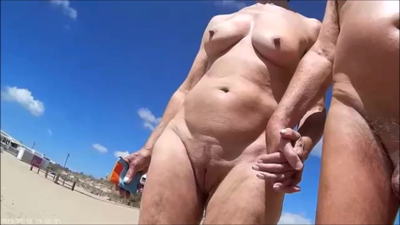 group of mature nudists walks around the beach naked | voyeurstyle