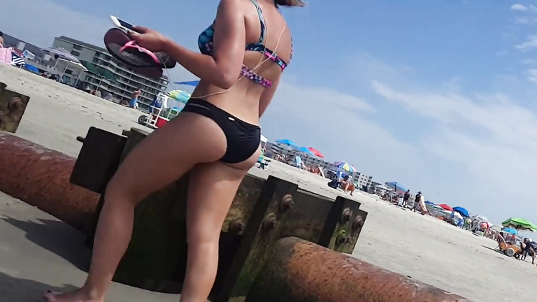 Saucy babe walks around the city beach in a colorful bikini