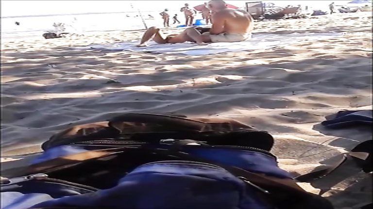 Seductive nudist girlfriend has her pussy exposed on the middle of the beach