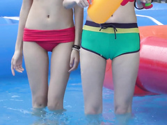 Two slim Japanese dolls have some fun in the kiddie pool