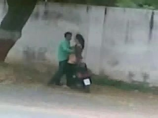 Pakistani couple bangs on a moped by the side of the road
