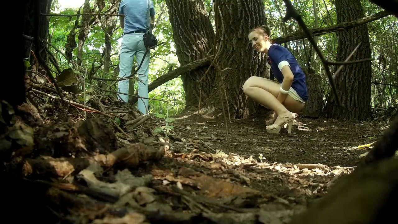 Guy stands on guard as his girlfriend pees behind a tree