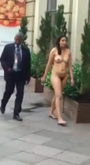 Long-haired woman takes a stroll around the town in the nude