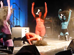 Painted boobs bounce around on the stage at a rock concert