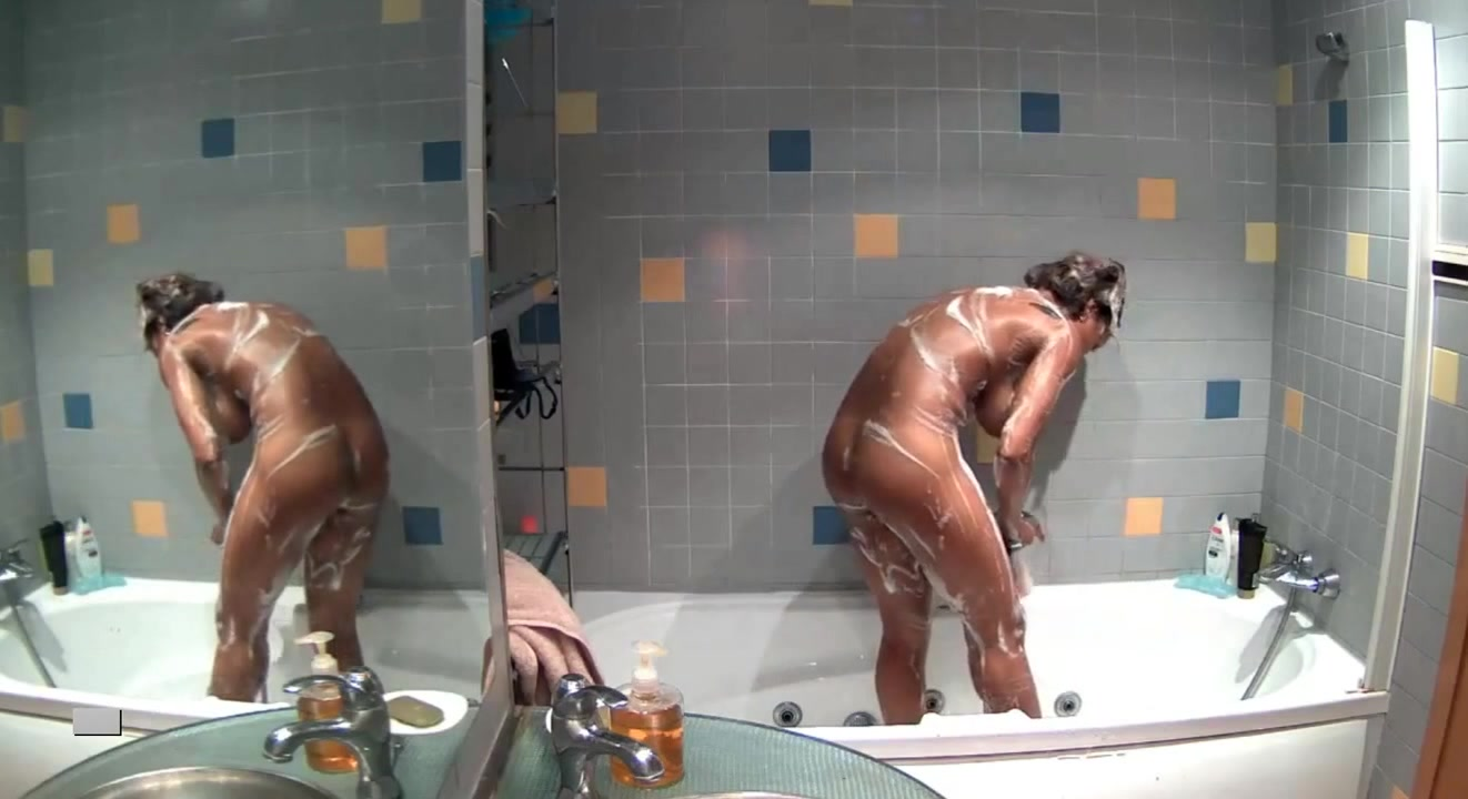 Long-haired babe soaps up while showering