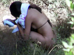 Brunette teen in bikini takes a leak in the woods