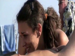 Beautiful brunette kisses his penis at the beach