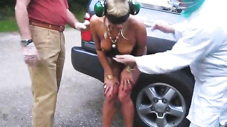 Gloved men fondle naked blonde on the street