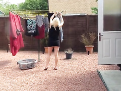 Housewife flashes her butt doing laundry out back
