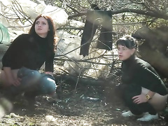 Women in turtlenecks and jeans relieve themselves in the woods