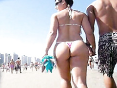 Curvy girlfriend in a pink thong walks the beach