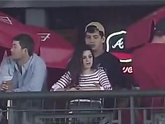 Fondling his cute girlfriend at a baseball game