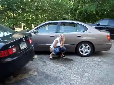 Laughing chick relieves herself in a parking lot