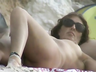 Mature woman is nude on the beach