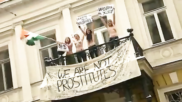 Topless protesters draw a crowd of admirers