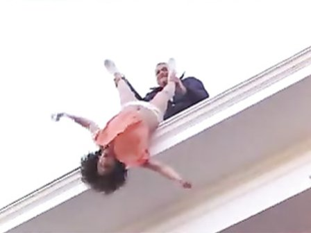 Woman in a dress dangled off the roof