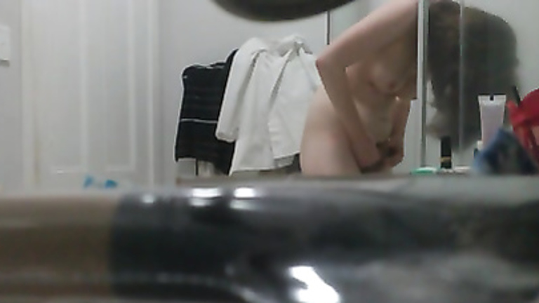 My girlfriend plays with her pubic hair on a bathroom cam