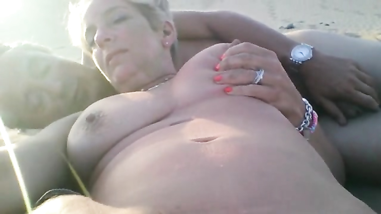 Lusty finger rubbing her clitoris on the beach