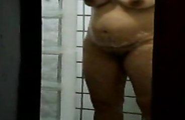 Pregnant woman scrubs her body hard in the shower