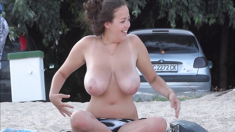 Busty topless girl smokes a cigarette