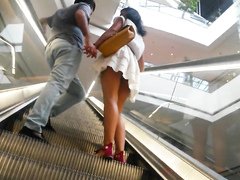 Short pleated skirt uppie on an escalator