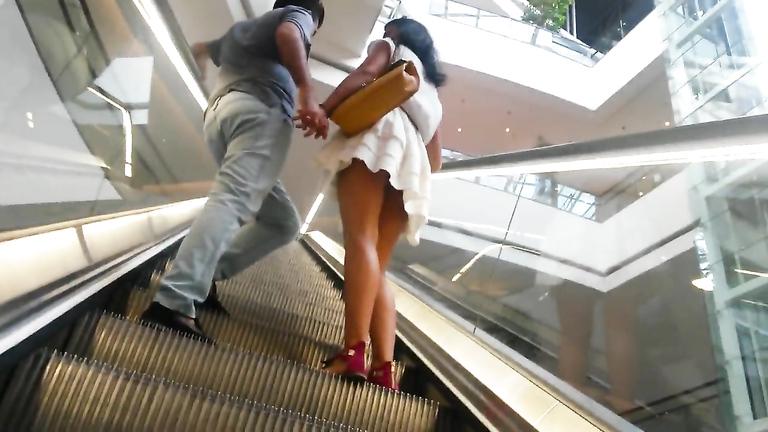Short pleated skirt uppie on an escalator
